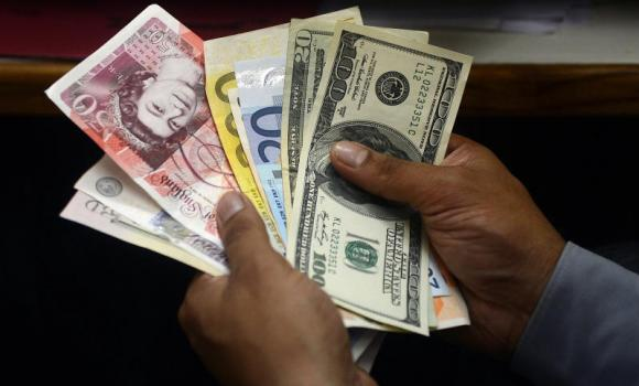 file-09-A money changer counts foreign currency notes in New Delhi. (AFP) 2